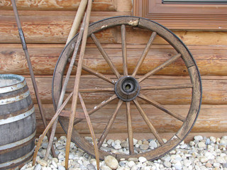 old cartwheel leaning against a wooden wall