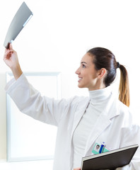 Attractive young female doctor examining x-ray results