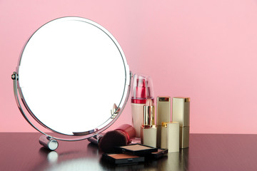 Round table mirror with cosmetics on table on pink background