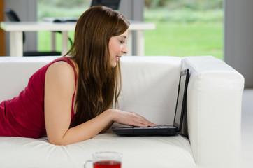 frau liegt auf der couch und tippt auf laptop