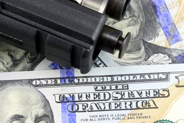 Hand Gun with American Currency - Financial Security