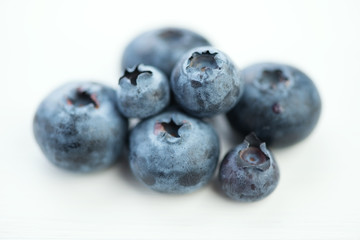 Macro shot of ripe blueberries, white wooden background