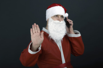 Portrait of Santa talking on mobile looking at camera, isolated
