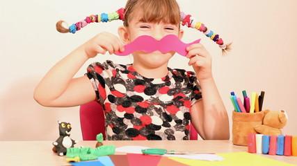 Wall Mural - little girl makes paper mustache