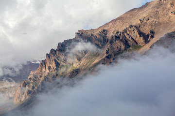 Fototapete - Mountain rocks covered by clouds