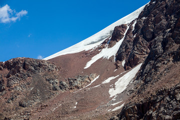 Fototapete - Snow slope of red mountain. Tien Shan