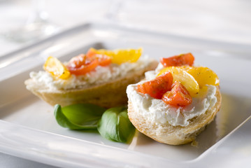 bruschetta topped with goat cheese and tomatoes.