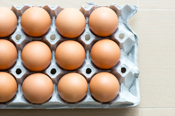 Eggs on the tray with light wooden background