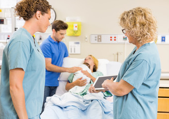 Nurses Discussing Report On Digital Tablet Against Couple With B