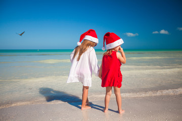 Rear view of Little cute girls in Christmas hats on the beach