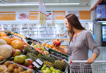 young woman in supermarket choosing fruits