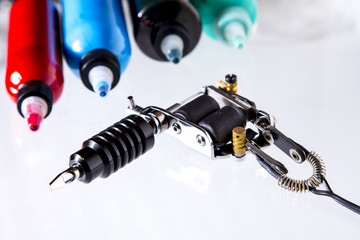 Tattoo gun with ink tubes on white background