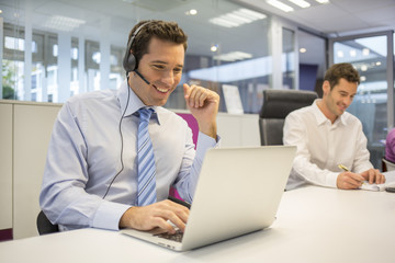 Businessman in the office on the phone with headset, Skype
