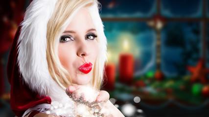 junge Weihnachtsfrau pustet Schnee