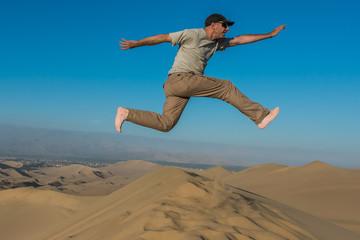 Fototapete - man jumping desert peruvian coast Ica Peru