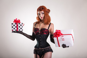 Portrait of pretty redhead pin-up girl holding gift boxes