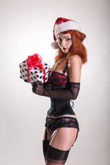 Pinup girl in Santa Claus hat, holding gift box