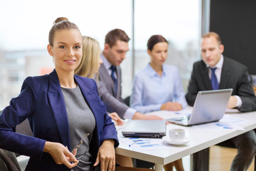 businesswoman with glasses with team on the back
