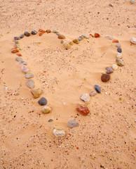 Heart of sea stones on sand