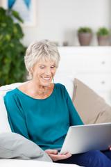 moderne ältere frau mit laptop zu hause