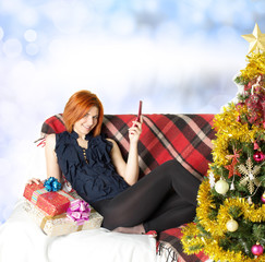 Happy girl on the sofa with a telephone and a gift box