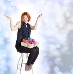 Joyful girl on a chair with boxes gifts