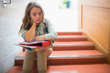 Upset student sitting on stairs Wall mural