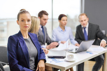 businesswoman in office with team on the back