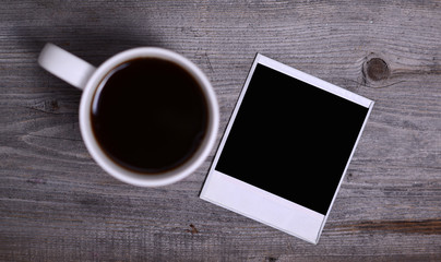 White mug of coffee and photo paper