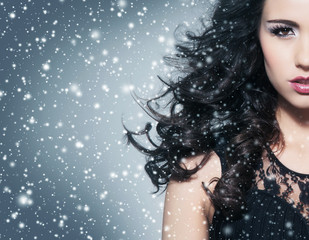 Portrait of a beautiful brunette woman on the snow