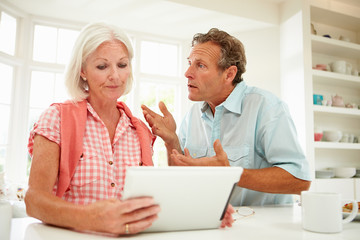 Worried Middle Aged Couple Looking At Digital Tablet