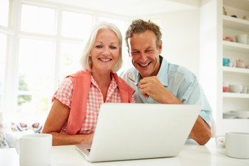 Smiling Middle Aged Couple Looking At Laptop
