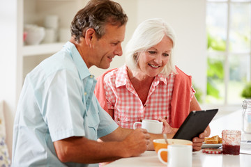 Middle Aged Couple Looking At Digital Tablet Over Breakfast