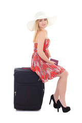 young beautiful blonde in red dress sitting on suitcase isolated