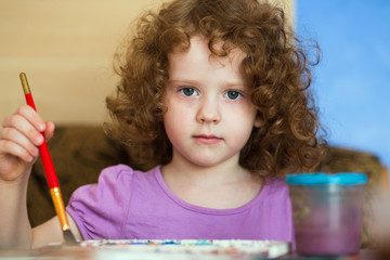 Little beautiful curly-haired girl draws
