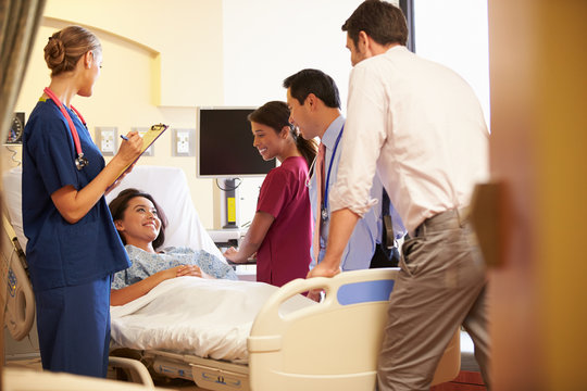 Medical Team Meeting Around Female Patient In Hospital Room