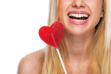 Closeup on smiling teenage girl with heart shaped lollypop