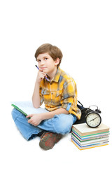 The boy sits with books, alarm clock and exercise book