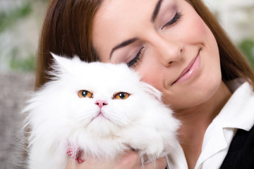 beautiful young woman holding a Persian cat