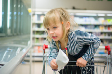 Adorable girl at shopping cart select iceream in supermarket