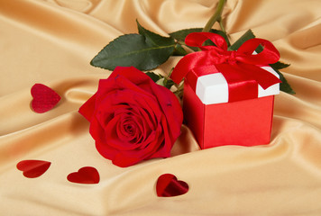 Red roses and gift box on golden fabric