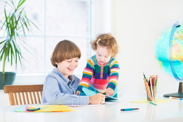 Happy children, young boy and his toddler sister, doing homework