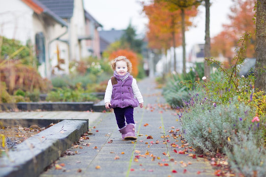 Adorable toddler girl walking down a beautiful road in a little