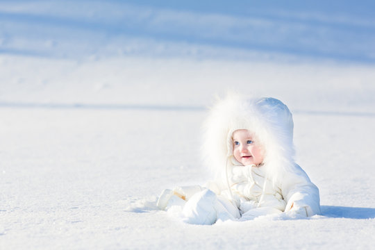 Cute little baby in a white jacket playing in snow