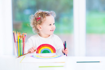 Happy smiling toddler girl drawing a rainbow next to a big windo