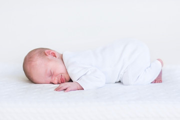 Little newborn baby sleeping on a white knitted blanket