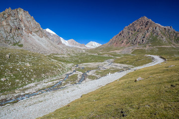 Fototapete - Mountain road along river. Tien Shan