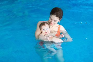 Mother and her baby in a swimming lesson in the swimming pool