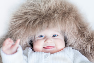 Funny baby girl with big blue eyes wearing a huge winter hat