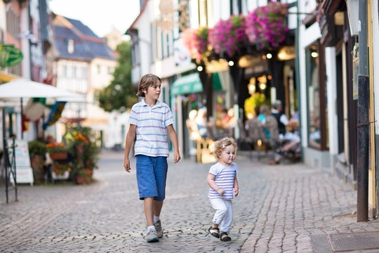 Cute school boy and his baby sister running in a historical city